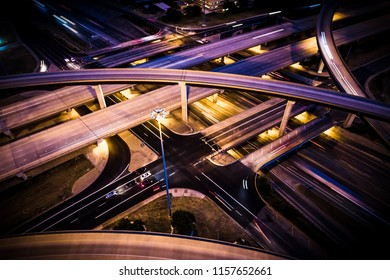 Driving at night . Highways interchange aerial drone view lights and cars headlights and brake lights city urban transportation highways