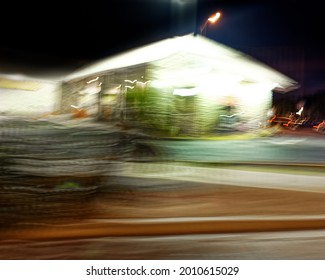 Driving at night, past a brightly lit gas station, the lights all motion blurred.