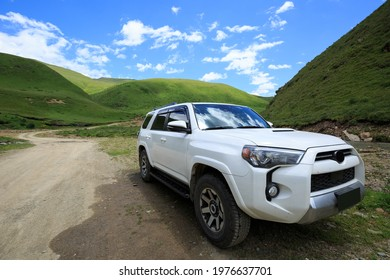 Driving offroad car on trail in high altitude mountains