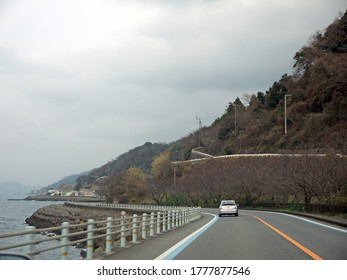 Driving on coastal highway with boxwood on roadside, distant mountains, travelling on Shikoku, Japan