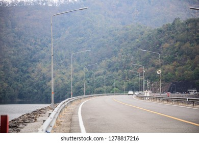 Driving on concrete road along the water reservoir dam in the area of rich natural forest tree mountain environment. Nature, Travel, Tourism, Ecotourism, Transportation, Environment concern concept
