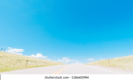 Driving on dirt road through open space in rural suburbia in Colorado.
