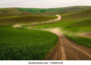 Driving on a dusty dirt road through dreamy wheat fields