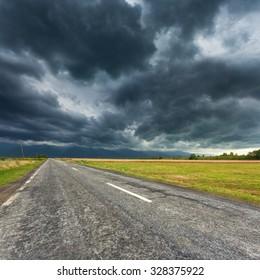 Driving on an empty asphalt road towards the Fagaras mountains with dramatic sky.