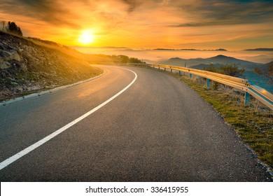Driving on an empty asphalt road towards the rising sun at autumn season in mountain area. Mountain Golija, Serbia.