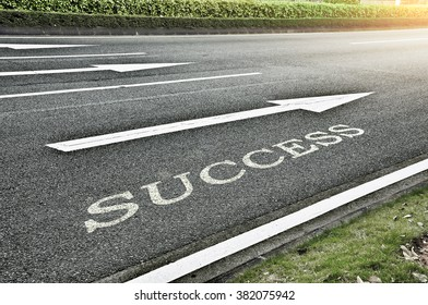 Driving on an empty asphalt road towards the destination and sign which symbolises success. Concept creative for success.