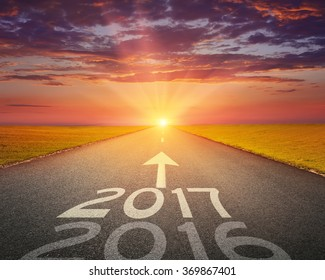 Driving on an empty road towards the setting sun to upcoming 2017 and leaving behind old 2016. Concept for success and passing time.
