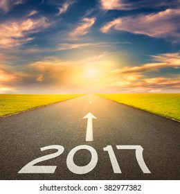 Driving on an empty road towards the sun to upcoming 2017 through idyllic scenery. Concept for success and passing time.