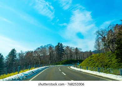 Driving on family road trip in Hokkaido, Japan on empty road with white snow on the side way. Empty snowy road with green trees on the side and mountain with bright blue sky in the background.