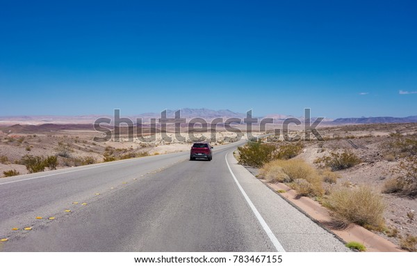 Driving on a high-speed highway leading to a mountains range. Panorama view of mountain and road in a sunny day for road trip background. Travel and active lifestyle concept. Nevada, USA.