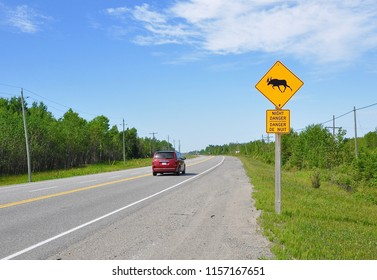 Driving on highway with moose and  night danger signs posted on the side of the road