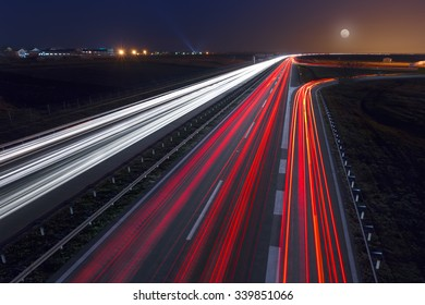 Driving on highway at night near Belgrade - Serbia. Light trails on motorway at night of full moon, long exposure abstract photograph.