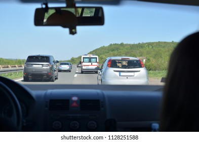 Driving on a highway with other vehicles and an ambulance car in front of him