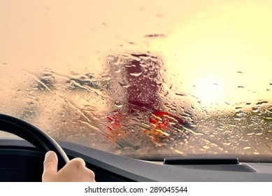 Driving on a Highway at Sunset - poor view caused by heavy rain and  back light