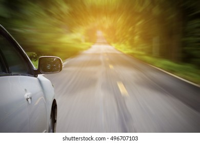 Driving on a road in national park with sunset light forward with heavy blurred motion.