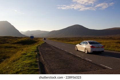 Driving on a road in the scottish highlands (Glencoe) during sunset