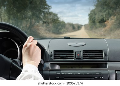 Driving on straight road. Female hand on car steering wheel. Copy space.