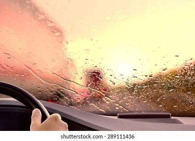 Driving onto a Highway at Sunset. Rainy weather rush hour traffic jam scene - poor view caused by heavy rain and  back light