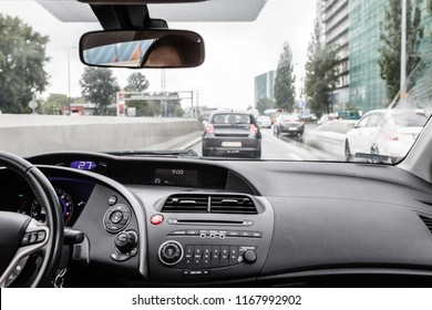 Driving a passenger car in traffic jam, view from inside on crowded road