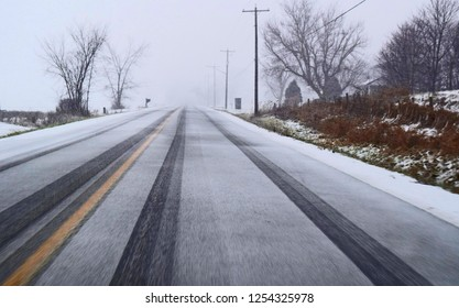 Driving in poor weather conditions on a wet, snowy road with rain, ice and sleet on a highway. Image ideal for safety posters, travelling warnings, televised reporting, etc.  with room for text.