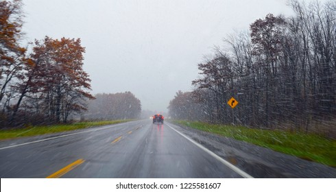 Driving in poor wintry weather conditions on a wet, snowy road with rain and sleet on a highway. Image ideal for safety posters, travelling warnings, with room for text.