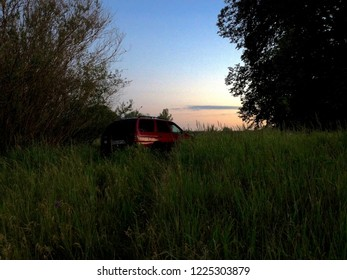 Driving a red station wagon along Polish riverbanks on a summer evening