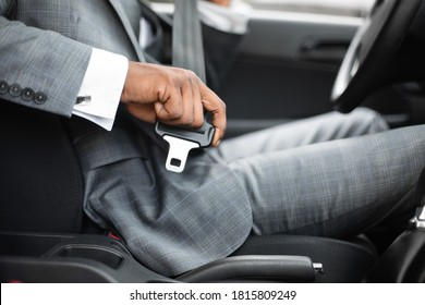 Driving safety concept. Unrecognizable black businessman fasten seat belt in his car, ready to go to office. African american man in stylish suit putting on his seatbelt before driving car, cropped
