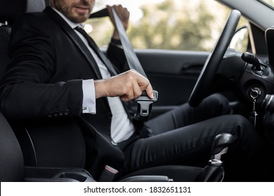 Driving safety concept. Unrecognizable businessman fasten seat belt in his car, ready to go to office. Man in stylish suit putting on his seatbelt before driving car to airport, cropped