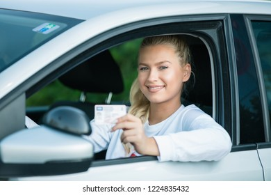 Driving school. Attractive young woman proudly showing her drivers license. Free space for text. Copy space.