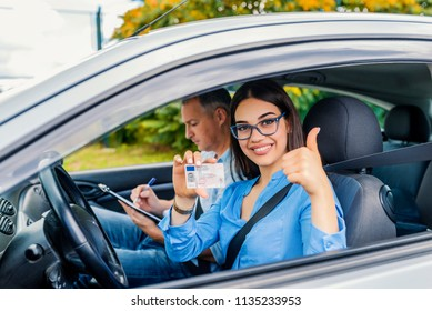Driving school. Beautiful young woman successfully passed driving school test. She looking sitting in car, looking at camera and holding driving license in hand. Girl with driving license