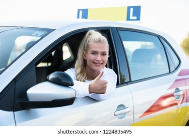 Driving school. Female young car driver going thumbs up after passing the driving license test. Successful woman smiling in vehicle. Free space for text. Copy space.