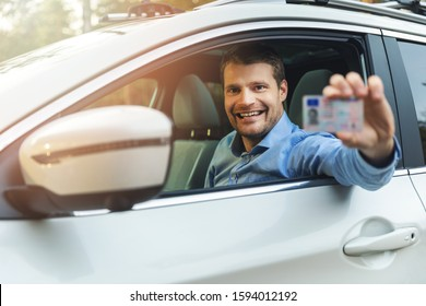 driving school - man sitting in the car and showing his driver license out of car window