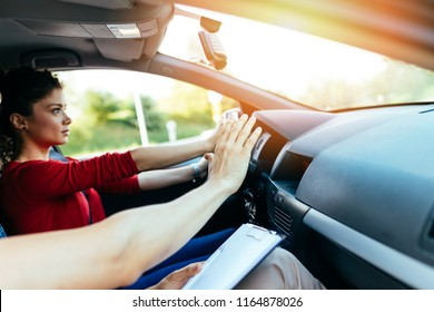 Driving school or test. Beautiful young woman learning how to drive car together with her instructor