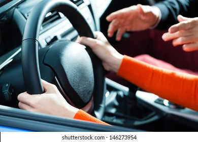Driving School - Young woman steer a car with the steering wheel, maybe she has a driving test perhaps she exercises the parking