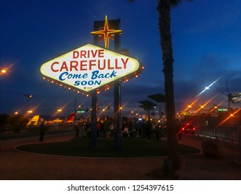 driving sign at the back of famous Las Vegas signature sign at night.