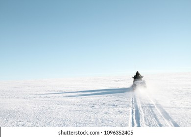 driving Snowmobile up a snow mountain in Longyearbyen, Svalbard - arctic expedition exploration - north pole alone blue sky