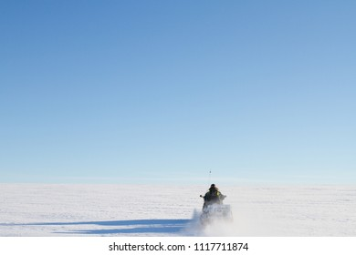 driving Snowmobile up a snow mountain in Longyearbyen, Svalbard - arctic expedition atmosphere - north pole alone blue sky winter landscape
