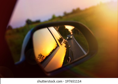 Driving at sunset - peek into a rear view mirror