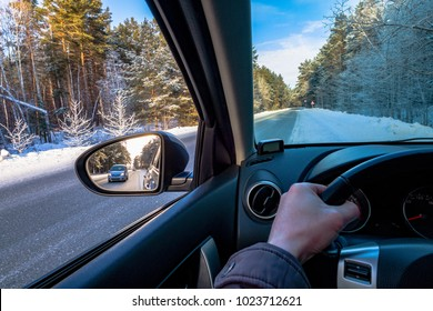 Driving SUV car in winter on forest road with much snow. rearview mirror. the car goes to overtake. auto makes overtaking.road view from inside the car