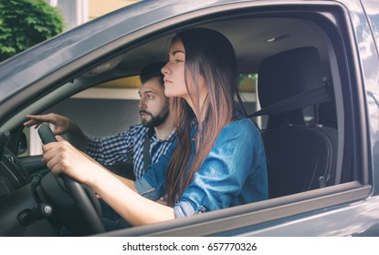 Driving test. Young serious woman driving car feeling inexperienced, looking nervous at the road traffic for information to make appropriate decisions. Man is an instructor, controlling and checking