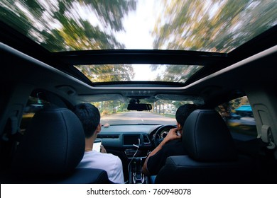 Driving for trip along country road in open top car sunroof