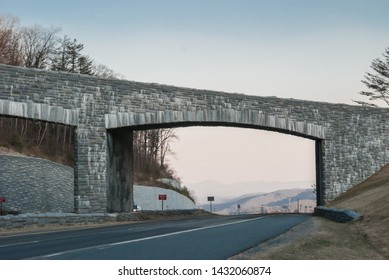Driving under a stone overpass along the Blue Ridge parkway in winter produces a clear view of the mountains to come