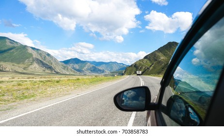 Driving view from side of car mirror mountain valley. Beautiful landscape of a road in the mountains on a sunny day