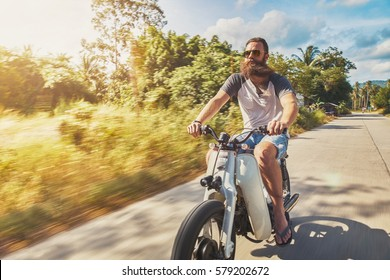 driving vintage motorbike fast through country side in Thailand shot with motion blur and lens flare effect