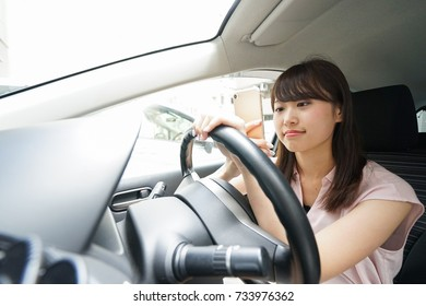 Driving woman using smartphone