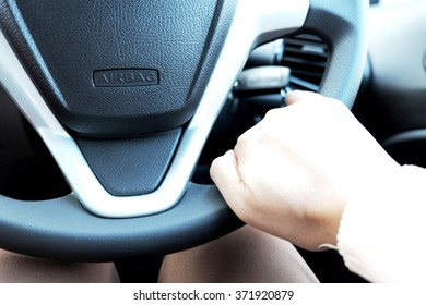 Driving/steering wheel with airbag and hand near sign. Focus on sign.