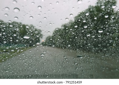 Drizzle on the windshield, Inside car when rainning, Road view through car window with rain drops.