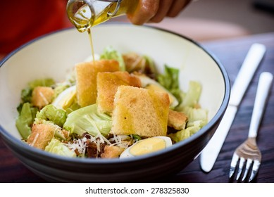Drizzling olive oil onto a Caesar-style salad.