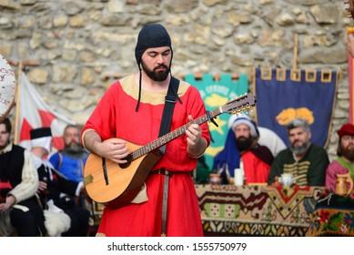DROBETA TURNU SEVERIN, ROMANIA - 08.31.2019: medieval guitar minstrel with fortress wall background