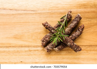 Droewors (biltong) with rosemary on a wooden board, this is a traditional food snack that can be found in South Africa. This image has selective focusing.